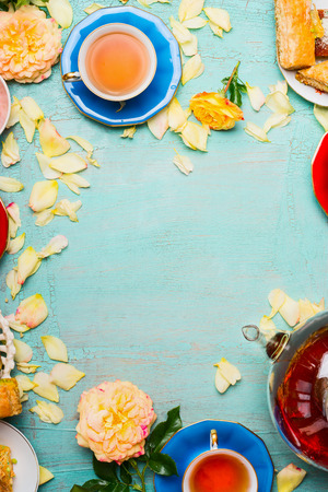 Cups of tea, pot , cakes and flowers petals on light blue background, top view, frame