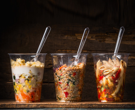 drink food: Healthy salads in plastic cups with fork on dark rustic background, side view. Take away lunch
