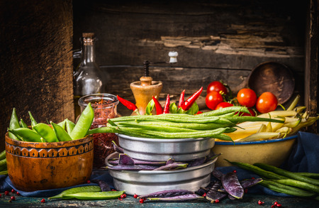 Various colorful pods peas and beans in bowls with cooking ingredients on dark rustic kitchen table with wooden background Imagens