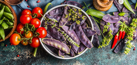 fruit background: Purple pea pods in metal bowl with tomatoes and cooking ingredients, top view.  Healthy vegetarian food concept Stock Photo
