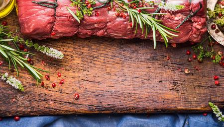 carne cruda: Raw asado con hierbas y especias atado con una cuerda sobre fondo de madera, vista superior, la frontera