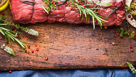 carne cruda: Raw roast beef  with herbs and spices tied with a rope on wooden background, top view, border