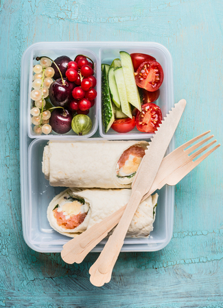 lonchera saludable con envolturas de tortilla de salmón y cubiertos de madera, frutas y verduras, vista desde arriba