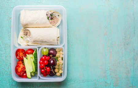 box: Healthy lunch box with tuna tortilla wraps , fruits and vegetables.