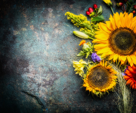 Sunflowers bunch on dark vintage background, top view, place for text