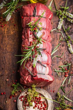 roast: Raw roast beef  with herbs and spices tied with a rope on wooden background, top view, close up