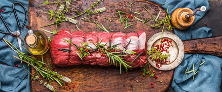 gefesselt: Raw roast beef  with herbs tied with a rope with cooking ingredients, oil  and spices on rustic background, top view, banner
