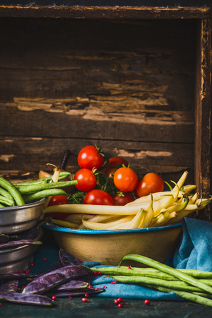 madera rústica: Various pea and beans pods with tomatoes  on rustic wooden  background Foto de archivo