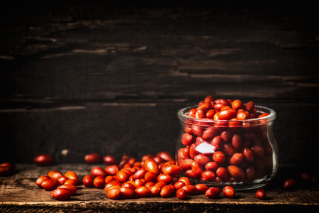 solanaceae: Fresh Goji berries in glass jar on dark wooden background, side view Stock Photo