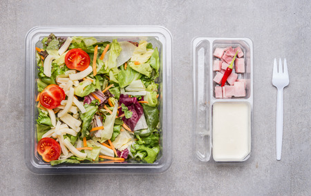 Healthy lettuce salad with cheese ,ham and yogurt dressing in lunch box, top view Stock Photo