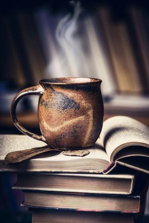 libros abiertos: Copa con bebida caliente y vapor en una pila de libros abiertos en la biblioteca, vista lateral