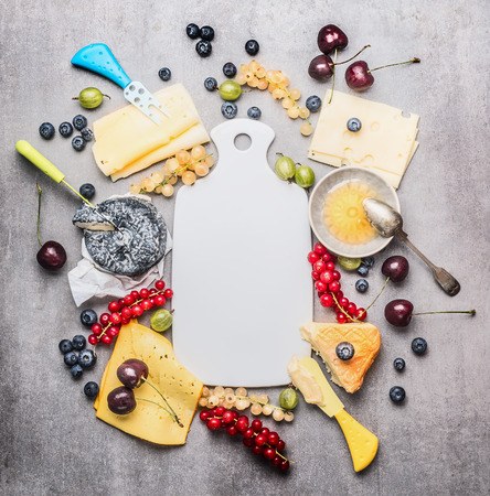 Blank white cutting board and various cheese with knife ,berries and honey, top view, frame