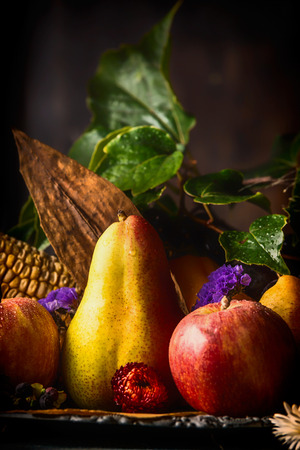 colorful still life: Autumn fruits on dark rustic kitchen table at wooden background, side view, close up, still life