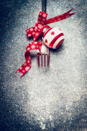 over: Festive Christmas table place setting with fork, red ribbon and ball on dark rustic vintage background, top view, close up