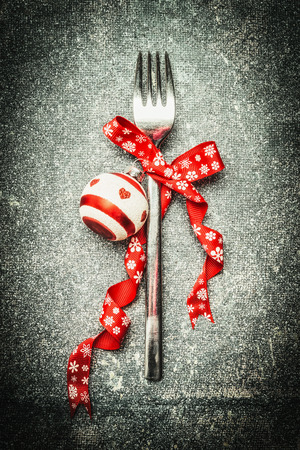 comida de navidad: Festive Christmas table setting with fork, red ribbon and ball on dark rustic vintage background, top view