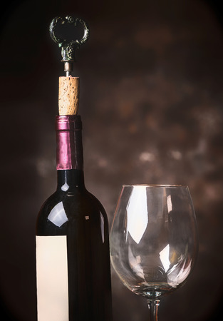 close up view: Bottle and glass of wine at rustic background,side view, close up