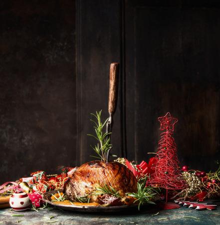 スタック フォークと木製の背景、側面図でお祭り休日の装飾付きのテーブル ローズマリー クリスマスのハムをテキストの配置します。