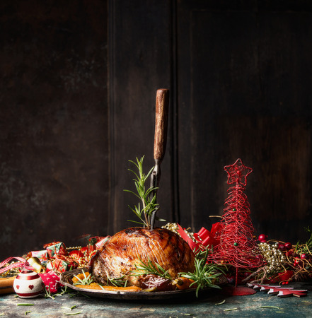 Christmas ham with stuck fork and rosemary on table with festive holiday decoration at wooden background, side view, place for text