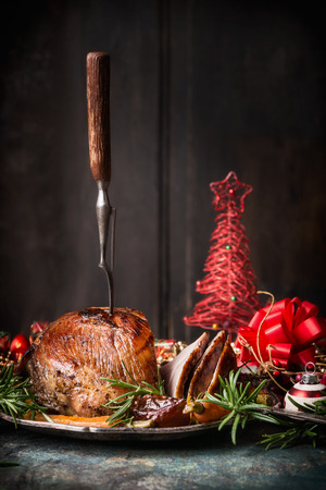 Roasted sliced Christmas ham with fork and red festive holiday decoration at dark wooden background, side view, place for text