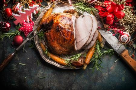 Tradicional rodajas de asado de Navidad presagiado jamón con decoración festiva de vacaciones sobre fondo oscuro rústico, vista superior, la frontera Foto de archivo - 64485548