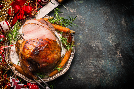 traditional christmas dinner: Roasted sliced Christmas ham on plate with fork, knife and festive decoration on dark rustic background, top view, border