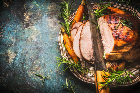 Roasted pork ham with kitchen knife and roast vegetables on dark rustic background, top view, border