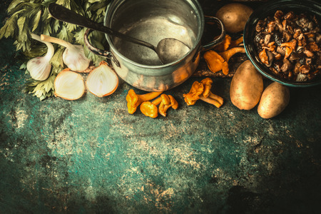 stew pot: Empty cooking pot with spoon ,forest mushrooms and cooking ingredients for soup or stew on dark rustic background, top view, border Stock Photo
