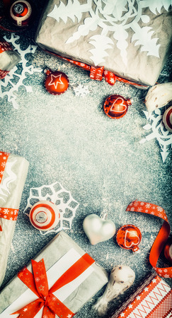 overhead shot: Various Christmas Gifts with handmade paper snowflakes and red festive holiday decorations on light blue vintage background, top view, frame