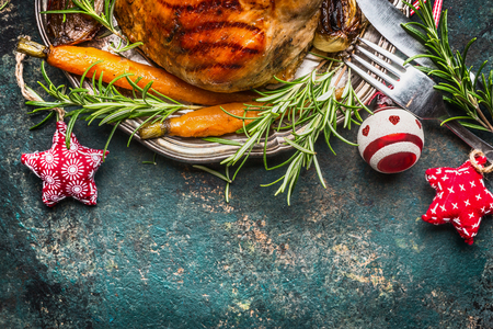 Roasted pork ham on silver plate with vegetables , cutlery  and Christmas decoration, top view, border Archivio Fotografico