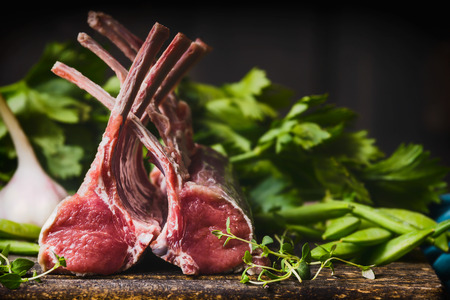 Rack of lamb, raw meat with bone on rustic kitchen table at wooden background, sideview Imagens