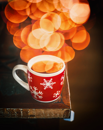 Red Winter snowflakes Cup with hot tea and bokeh on dark rustic table, side view
