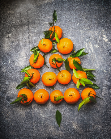 tangerine tree: Christmas tree make with tangerines on dark rustic background, top view, festive greeting card