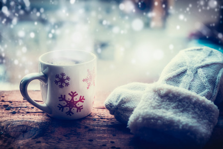 Snowflakes Mug with hot beverage and knitting mittens on frost window sill at winter snow nature background