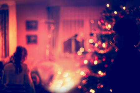 home lighting: Blurred home Christmas scene with Christmas  tree, gifts , festive bokeh lighting and silhouette of girl Stock Photo