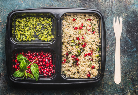 box: Healthy vegetarian lunch box with  quinoa salad with pomegranate and pistachio, top view