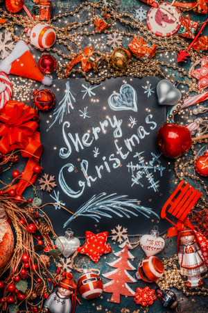 Merry Christmas lettering on dark chalkboard and various red holiday decoration on dark rustic background, top view, frame. Festive greeting card Stock Photo