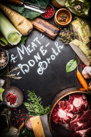 huesos: Varios ingredientes de cocina saludable para la carne de caldo de hueso con letras en la pizarra oscura, vista superior, marco