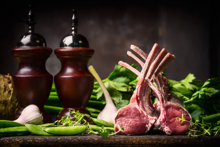 Lamb dish cooking with fresh lamb racks from butcher on dark rustic kitchen table at wooden background, top view
