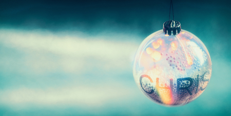Transparent Christmas ball with shine and bokeh on blue light background, banner