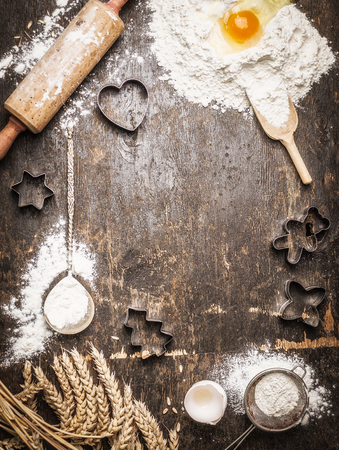 vintage photo: Christmas baking background with ingredients and  tools: Cookie Cutters, Cups, Mats, Rolling Pin, spoon . Dark, rustic, top view, frame