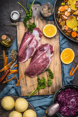Raw Duck breast with ingredients for tasty cooking: oranges,vegetables,  dumpling and red cabbage on cutting board at dark rustic kitchen table, top view. German cuisine concept