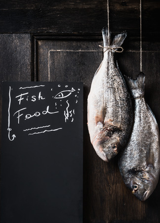 black fish: Two dorado fishes hanging on a rope at dark rustic wooden background, beside standing black chalkboard with Fish food lettering Stock Photo