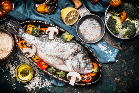 Fish dishes cooking preparation with dorado in backing form in shape of fish with healthy  vegetables on dark rustic background with ingredients, top view. Seafood concept