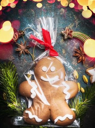 bolsa de pan: Galleta del hombre de pan envuelto en celofán y atado Bolsa con fiestas de cinta en el fondo de la vendimia con la iluminación bokeh de vacaciones, vista desde arriba