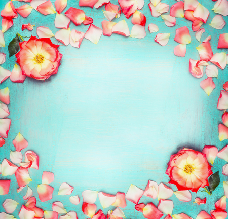 Flowers frame with roses and petals on turquoise  blue shabby chic background, top view, place for text
