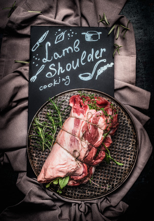 string top: Lettering lamb shoulder cooking on black chalkboard with raw  lamb shoulder roast with string ,  Filled with herbs and spices on vintage baking tray , top view. Meat food.