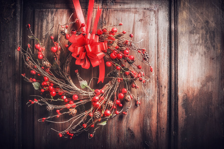 white door: Handmade Christmas wreath hanging on dark wooden door with red ribbon and berries , front view, retro styled, place for text