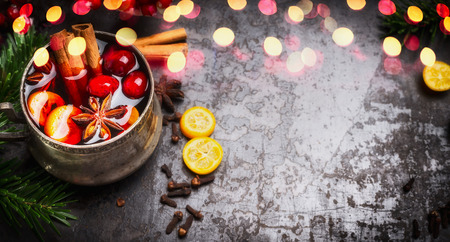 wine background: Banner with mulled wine cup and spices on dark rustic background with bokeh
