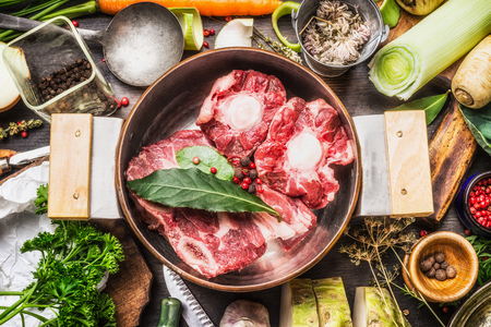 Cooking pot with  soup or bone broth meat and vegetables cooking ingredients and spices on kitchen table, top view
