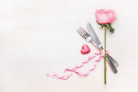 Table place setting : rose flower, cutlery and ribbon on light background, top view, place for text